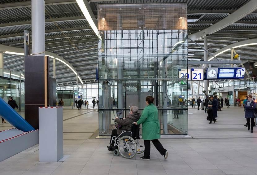 Toegankelijkheid openbare gebouwen. Vrouw in een rolstoel op Den Haag Centraal