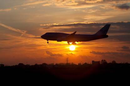 Vliegtuig met op de achtergrond een ondergaande zon.