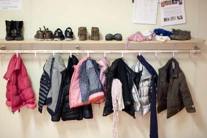 Kapstok waaraan jasjes hangen en een plank met schoentjes daarboven in een kinderopvanglocatie