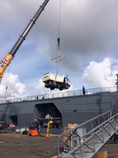 Een vrachtwagen wordt vanaf de kade van Den Helder met een enorme kraan aan boord gehesen van de Zr Ms Karel Doorman